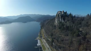 Fly away from Bled castle on a sunny day 4K. Aerial shot of famous old castle over the top of lake Bled on a beautiful weather and crystal blue water.