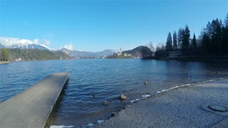 Flying above lake pier with beautiful tranquil view in 4K. Ascending from land over pier with view on lake Bled and famous church on island in the middle. Beautiful sunny day with blue water.