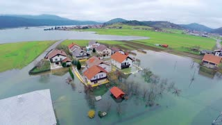 Flying around houses in flooded water. Aerial shot over homes after flooding disaster in countryside with houses in water.