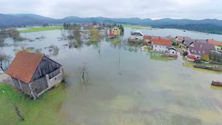 Flying close to flooded water. Aerial shot of flooded area in countryside of Slovenia. Houses in water, farmland and objects flooded.