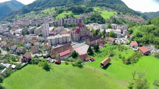 Flying over a small city in a green valley. Aerial footage of Zagorje ob Savi city in Slovenia on a sunny day, with tall blocks rising to the sun.