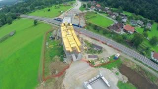 Flying over bridge built over railway. Aerial flight over construction site building a bridge over railway tracks.