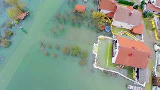 Flying over house with flooded backyard. Direct above view of homes in water after flooding in Slovenia. Aerial shot.