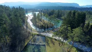Flying over lake in forest with reflections from river. Beautiful nature from air on a sunny day and landscape view above. Tall trees around and hill far away. Shoot from quadcopter in 4K
