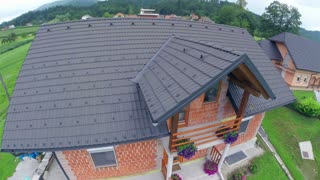Flying over new built house roof. Aerial shot of house roof and village behind.