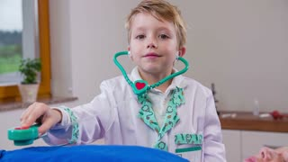 Fresh genius doctor using stethoscope. Little boy playing doctor looking in camera while checking patients stomach with Stethoscope in slow motion.