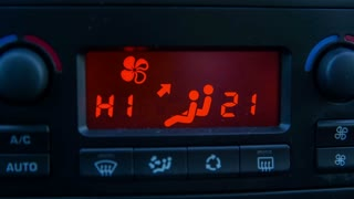 Front shot of high temperature value in car. Static shot of car ventilation dashboard LED screen.