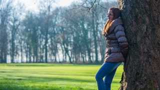 Girl enjoying sunshine in cold days. Wide handheld shot of attractive woman adult happy smiling in forest, leaning on tree and looking of camera.