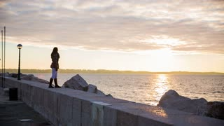 Girl slowly walking in front of sea sunset.Wide panning shot of attractive woman at sea walking on stone pier with sunset in background.