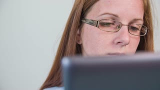 Girl with glasses using tablet computer close up. Attractive young woman with red hair and long nails lying on bedroom bad and playing/typing on tablet computer. Slow motion jib shots.