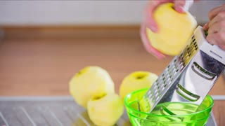 Grating apple in to bowl. Person in kitchen grating few apples with kitchenware tool in to green bowl close up.