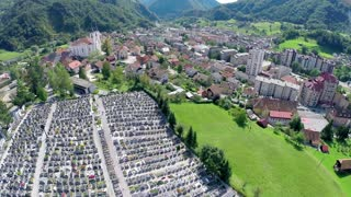 Graveyards tombstones and city in background. Aerial shot over graveyard and valley city Zagorje in background on a sunny day.