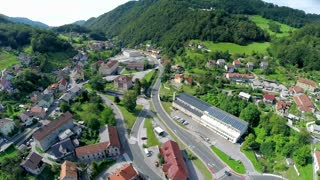 Green valley with small town aerial shot. Lifting over Zagorje ob Savi city landscape on a sunny day.