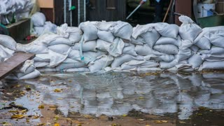 High wall of sandbags in flood. House owner puts wall of sandbags around own home.