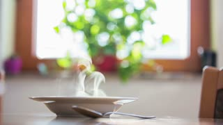 Hot soup with kitchen window.Close up of kitchen dish with soup in plate with hot soup and window with green flower.