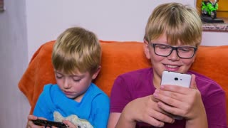 Interested in games on smartphone. Brothers in living room enjoying on sofa playing games on smartphones. Jib shot of kids using technology toys.