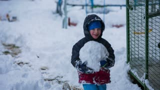 Kid carry big snowball and throw in to brother. Tracking young kid walking and holding big cold snowball in size of ball, throwing in to older brother.