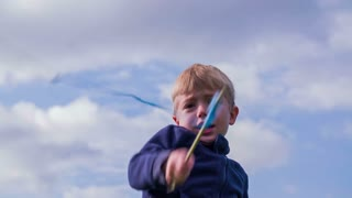 Kid spinning ninja sticks and cutting with sword. Cute blond young boy playing ninja swordsman outside in slow motion.