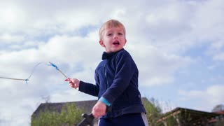 Kid swing around sword and sticks in slow motion. Medium shot of young boy playing sword man with waving around sword and roped sticks.