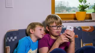 Kids enjoy playing with smartphone. Jib shot in living room with two brothers looking in one smartphone. Kids using technology, playing games.