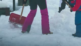 Kids playing in snow close up on legs. Winter day with kids in warm clothes play in white cold snow.