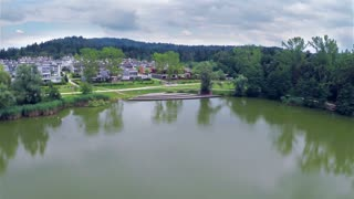 Lake with wooden dock aerial flight. Small lake near suburban apartments, with park and dock. Flying over.