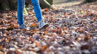 Legs kicking through fall leaves close up. Low angle view of woman feet walking through forest full of dried leaves in fall.