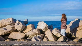 Leisure walk around the rocky sea beach. Female person walking on stone beach on a sunny day.