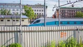 LJUBLJANA, SLOVENIA - AUGUST 2014: Passenger train bullet from behind the fence.Static shot of blue passenger train passing on a sunny day.