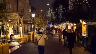 LJUBLJANA, SLOVENIA - DECEMBER 2014: Busy stalls district around Christmas at night. Shopping district with small wooden stalls selling Christmas goods, people wondering around at night.