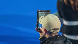 LJUBLJANA, SLOVENIA - JANUARY 2015: Person with tablet computer video recording. Close up of coach video recording competitors at dog exhibition with big screen tablet computer.