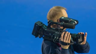 LJUBLJANA, SLOVENIA - JANUARY 2015: Television camera guy. Person with big professional camera shooting event for television.
