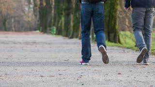 LJUBLJANA, SLOVENIA - NOVEMBER 2014: People walk in park. Close up tracking two person walk on grave path in promenade.