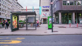 LJUBLJANA, SLOVENIA - SEPTEMBER 2014: Driving by a bus stop with many terminals and people waiting. Bavarian Palace bus stop in Slovenia from cars perspective in slow motion.