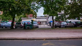 LJUBLJANA, SLOVENIA - SEPTEMBER 2014: Small bus stop with buildings in background driving by. Slow motion driving with car on road and shooting through side window.
