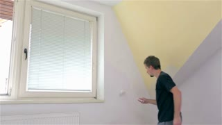 Male painting walls around windows. Young man in new apartment painting walls before moving in.