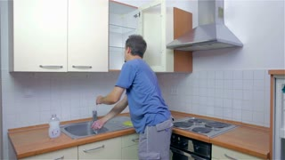 Man cleaning kitchen with sponge. Young attractive man in new home, checking and cleaning kitchen before using with own dishes.