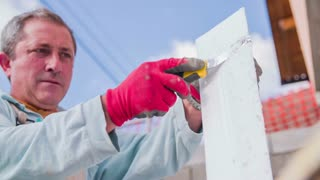 Man cutting Styrofoam with sharp knife. Slow motion medium shot of male person in working clothes cut part of Styrofoam white block for isolation of house.