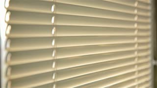 Man peeping trough blinds at sunrise