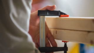 Man Sawing Wooden Bars With Small Saw