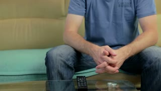 Man sitting on couch picking remote controller and leaving.
