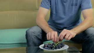 Man sitting on sofa with dish of grapes in front and pulling them off and eating.