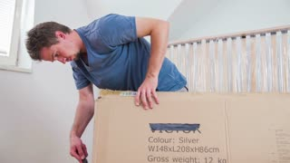 Man unpacking big box with knife. Slow motion shot of man with knife un-boxing new stuff.