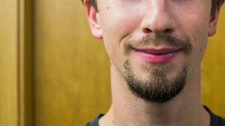 Man with stylish beard smiling in to camera close up. Person in bathroom smiling in camera close up on mouth and beard around.