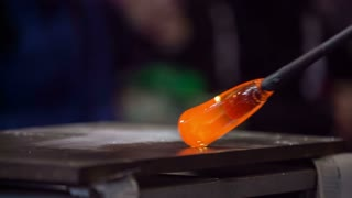 Melted glass designing close up. Person working with long stick with melted glass glowing at the end and rolling on iron table.