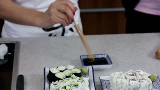 Mixing Wasabi in Soy sauce. Professional Asian woman cook preparing sushi and maki-zushi dish from rice and other healthy ingredients.