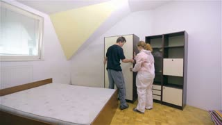 Moving big closet away from wall. Wide shot of whole room with young man and woman in protective suit moving furniture away from wall.