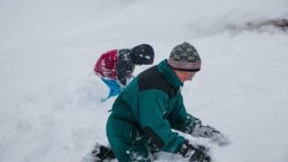 Older boy bury kid under snow. Little kid snowballing older brother, which revenge by burying kid under pile of snow.
