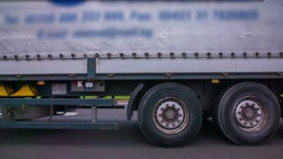 Overtaking truck on highway in slow motion. Side car windows shot of truck with trailer, passing by.