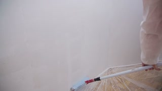 Paint roller going up and down in slow motion. Person painting walls with paint roller in slow motion.